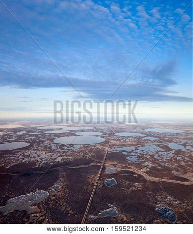 Aerial view of the oilfield in tundra in autumn. Some gas pipelines running from gas field in tundra. Oil processing plant is located in the foreground.