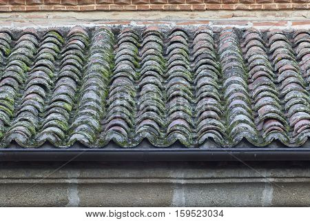 Old roof tiles with a black steel gutter to get the rain water.