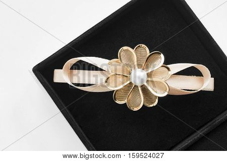 Golden flower shaped barrette in black jewel box closeup