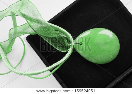 Green nephrite necklace in black jewel box closeup