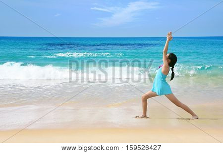Young healthy Asian kid doing yoga on tropical beach in warrior pose I. Preteen girl in swimwear practice yoga on sea beach blue sky sand sun daylight relaxation landscape for sun protection ad.