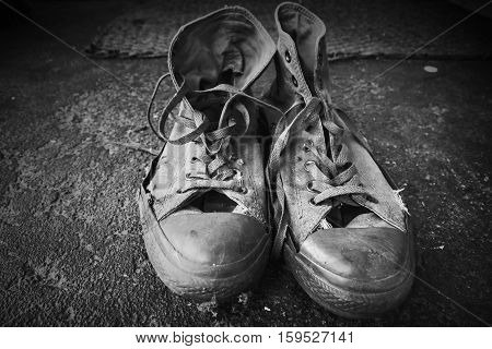 Old Sneakers Standing On Concrete Floor