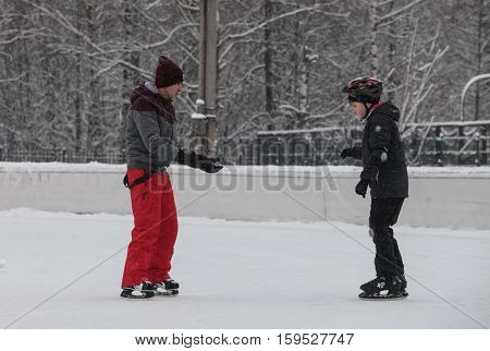 Saint-Petersburg Russia - December 2 2016: Urban outdoor ice rink in the park. Two boys are learning to skate.