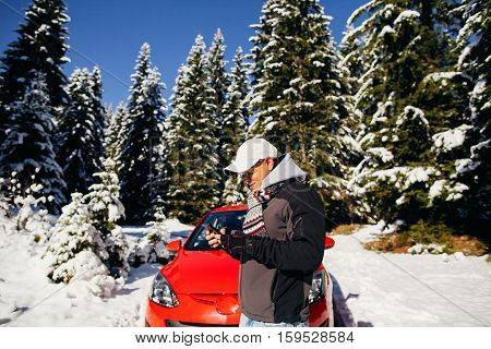 tourist male travel by car with smartphone in snowy forest. Winter pine forest background.