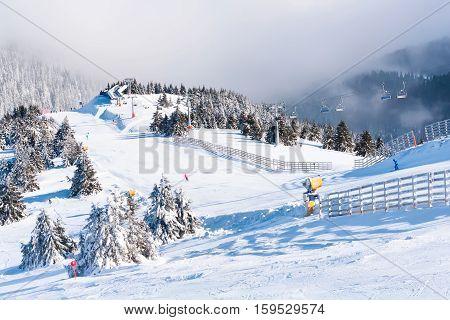 Ski resort, ski slope, ski lift, pine trees and fog mountains panorama