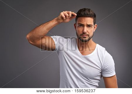 A serious handsome young man combing his hair in a white t-shirt