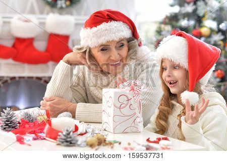 Portrait of exited grandmother and her little cute granddaughter sitting at the table with Christmas gifts
