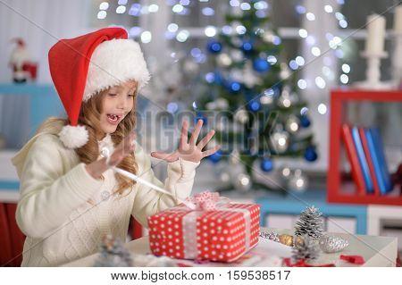Portrait of exited little girl in Santa hat with het present