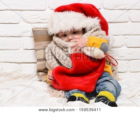 small baby boy with adorable curious face in red sweater with dummy in new year hat scarf and christmas or xmas stocking or boot on white brick wall background
