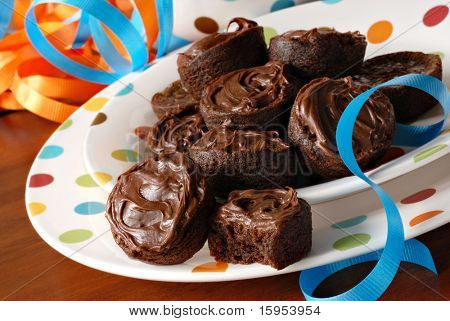 Chocolate frosted brownie bites on festive polka dot plates with colorful ribbons.  Macro with shallow dof.