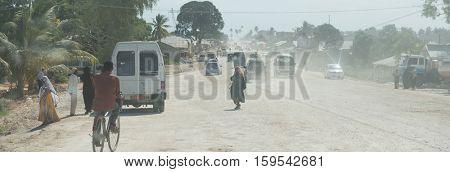 ZANZIBAR, TANZANIYA- JULY 14: dusty road with transport and walking people leading to Zanzibar town on July 14, 2016 in Zanzibar