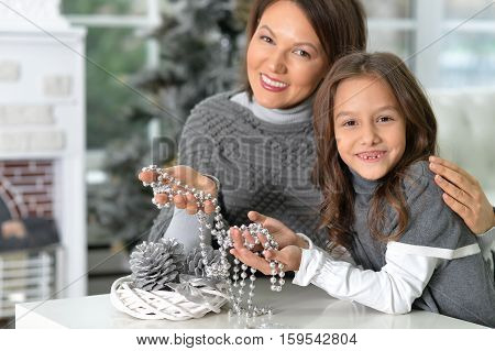Portrait of ypung mother and her daughter with Christmas decorations sitting at the table