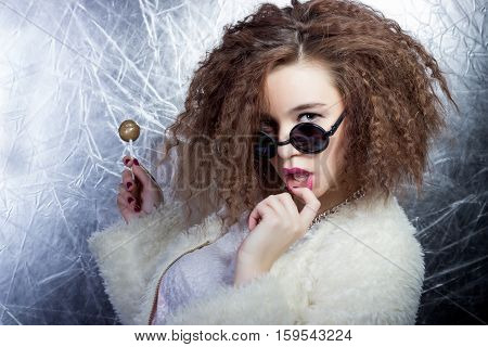 funny mischievous cheerful girl smiling with curly hair in a white blouse and jeans in the sun round glasses with candy in studio