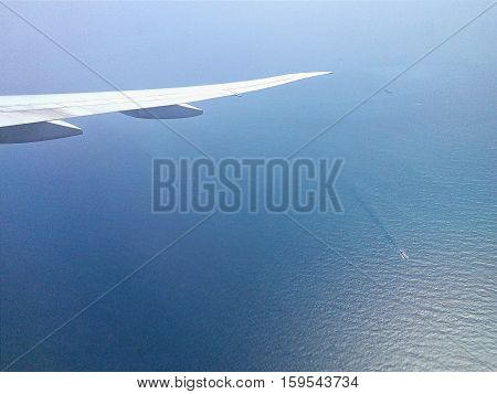 Aircraft Wing Above Calm Sea With Still Water And Ships Sealing. Flying Over The Clean Blue Sea. Air