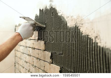 Installing the tiles on the wall. A worker setting tiles in the form of brick. He put adhesive using a comb trowel.