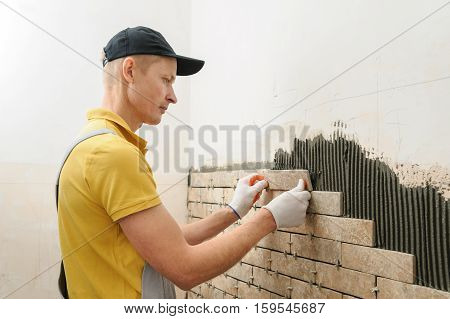 Installing the tiles on the wall. The worker putting tiles in the form of brick.