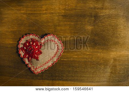 Heart of handwork with a pattern placed on a wooden background. Valentine's Day background. Copy space.
