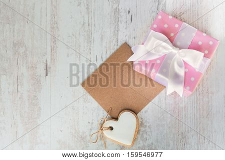 Top view of a gift box wrapped in pink dotted paper heart shaped love cookie and an empty kraft card over a white wood background.