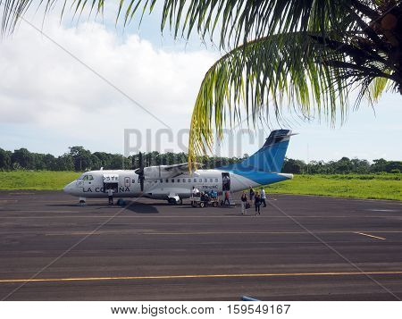 BIG CORN ISLAND NICARAGUA-AUG. 27: Tourists disembarking from twin prop La Costena Airline plane on tarmac airport of Big Corn Island Nicaragua Central America on August 27 2016.