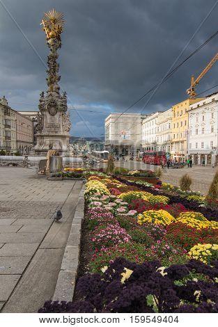 LINZ, AUSTRIA - October 30, 2016: Baroque Trinity column and autumnal flower decoration on the main square (Hauptplatz) in Linz Austria