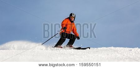 Male skier in orange ski jacket skiing down a ski run at ski resort on a sunny winter day.