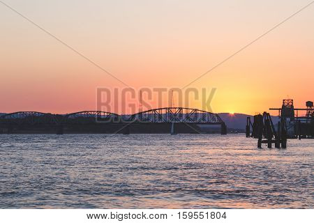 Sun setting over Columbia River between Portland, Oregon and Vancouver, Washington, USA. Railway bridge and mountains in the distance.