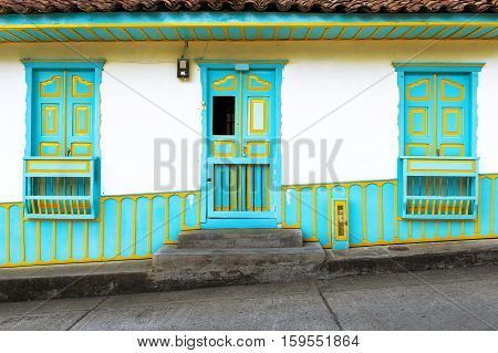 Detail of a wooden door and windows painted in bright colors in a traditional colonial house in the town of Salento in Colombia South America; Concept for traveling in South America and Colombia
