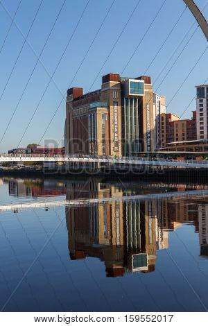 Newcastle England - October 25 2016: Gateshead Millennium Bridge and the Baltic Centre for Contemporary Art and their reflection in River Tyne. The bridge spans the River Tyne in north east England.