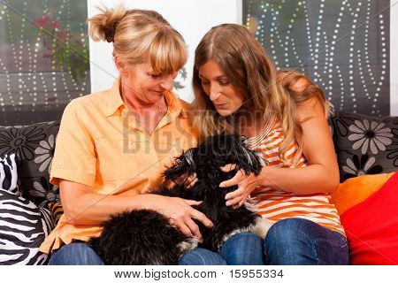 Two women presumably mother and daughter playing with a dog in her home