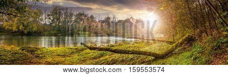 Mountain River With Fallen Tree On The Shore At Sunset