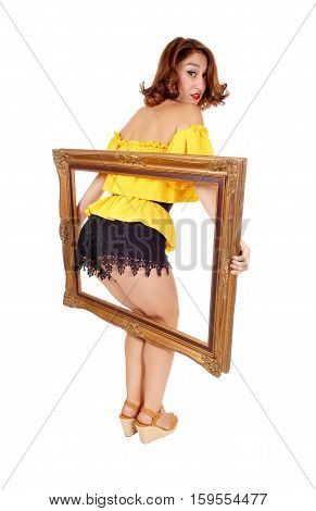 A surprised woman in a yellow blouse and black shorts putting her bottom trough a picture frame isolated for white background.