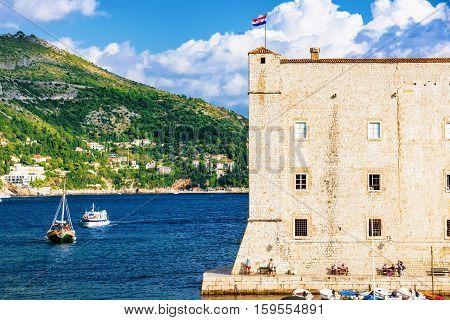 DUBROVNIK CROATIA - SEPTEMBER 22: Castle wall and harbor area of Dubrovnik's seafront with boats and nature on September 22 2016 in Dubrovnik