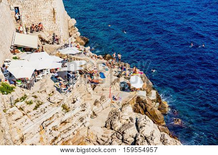DUBROVNIK CROATIA - SEPTEMBER 22: This is a rocky seafront area outside the fortress wall of Dubrovnik where tourists come to swim and sunbath on September 22 2016 in Dubrovnik