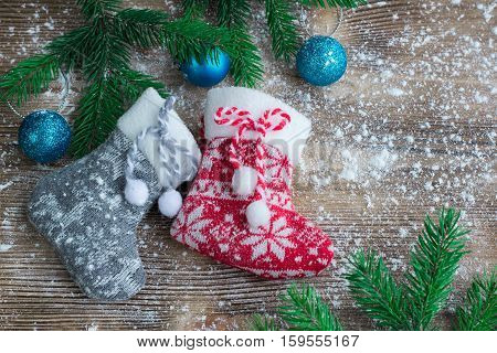 Two Christmas Stockings On Snowbound Wooden Background, Blue Balsl Ornaments