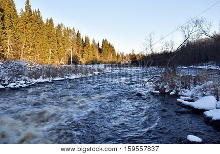 A little river with streaming water and the midwinter sun shining on the forest on one side picture from the North of Sweden.