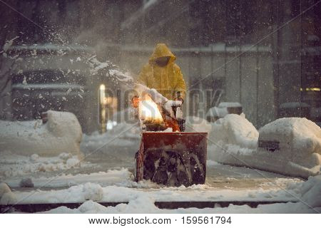 man with a snow blowing machine working and cleaning the city street in winter day during snow blizzard in New York City