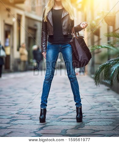Fashionable young blonde girl with long legs wearing blue jeans leather brown coat and holding a bag walking and shoppin on city street in old town