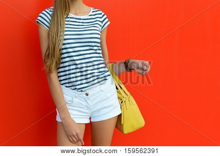 Female summer outfit with short white shorts striped t-shirt and leather yellow bag. Beautiful girl holding colorful bag and standing near red wall.