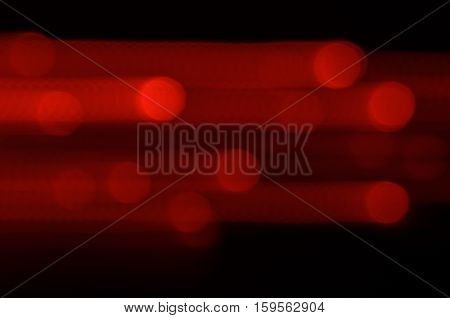 Red Lights In Movement. Blurred Red Background With Lights In Movement Going Right.