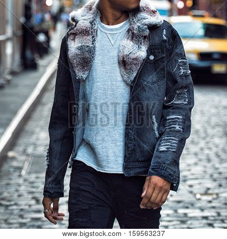 Fashionable winter jeans coat with fur and cuts on male model walking on city street. Winter autumn collection street style casual outfit.
