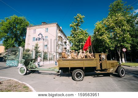 Gomel, Belarus  - May 9, 2016: Russian Soviet Military Truck ZIS-5V With Men In Soldiers Uniform On Board, Weapon, Red Flag Of WW2, Towing ZiS-2 57-Mm Anti-Tank Gun. Prepare For 9 May Victory Parade
