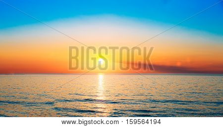 Sun Is Setting On Horizon At Sunset Sunrise Over Sea Or Ocean. Tranquil Sea Ocean Waves. Natural Sky Blue And Orange Colors. Panoramic View, Panorama.