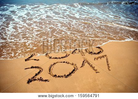 New Year 2017 is coming concept - inscription 2017 and 2016 on a beach sand the wave is covering digits 2016. New Year 2017 celebration on New Year tropical island travel tour.