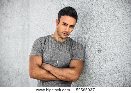 Portrait of young adult stylish handsome man with bristle standing outdoors and leaning on wall with arm crossed wearing grey casual t-shirt