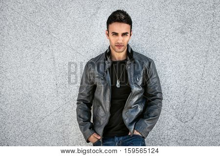 Handsome fashion man posing near the wall wearing grey leather coat black t-shirt and jeans.