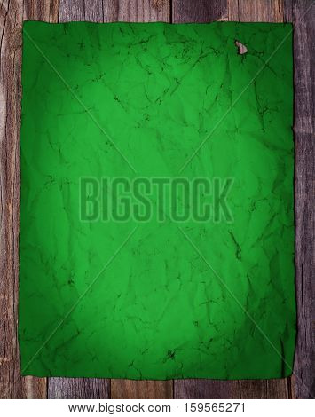 Blank page of old green vintage paper on wooden background