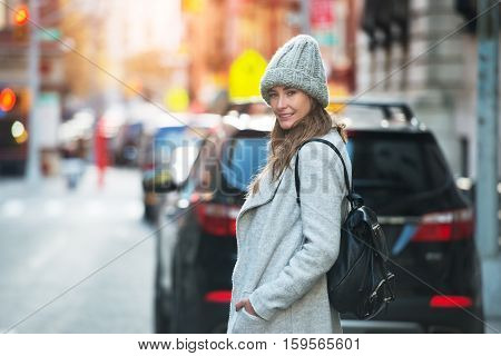 Young adult woman walking on city street wearing hat and jacket with backpack. Winter fashion woman outfit style.