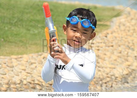 Japanese boy playing with water gun (4 years old)