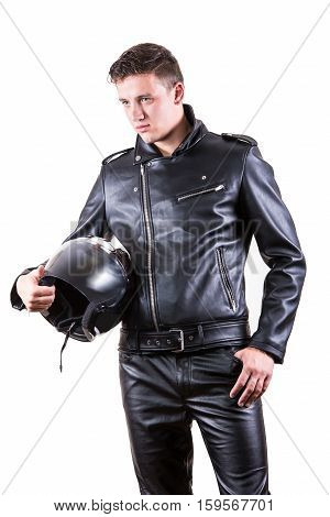 Portrait of handsome biker man wearing black leather jacket and pants holding motorcycle helmet and looking at the camera