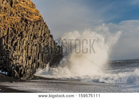 Huge wave crashes with Reynisdrangar, basalt sea stacks situated under the mountain Reynisfjall near the village Vik, Iceland. In February 2016 a Chinese tourist was found dead, perished in the waves.